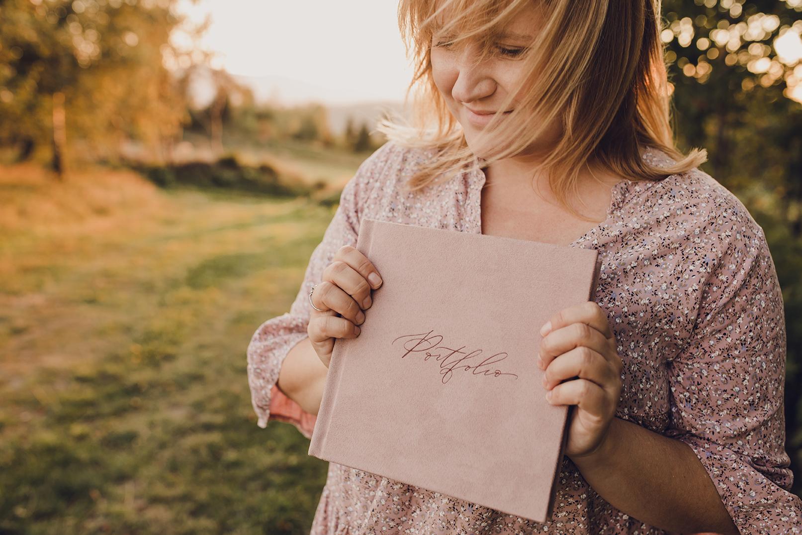 dziewczyna trzyma album fotograficzny, pudrowy róż, napis portfolio, crystal albums