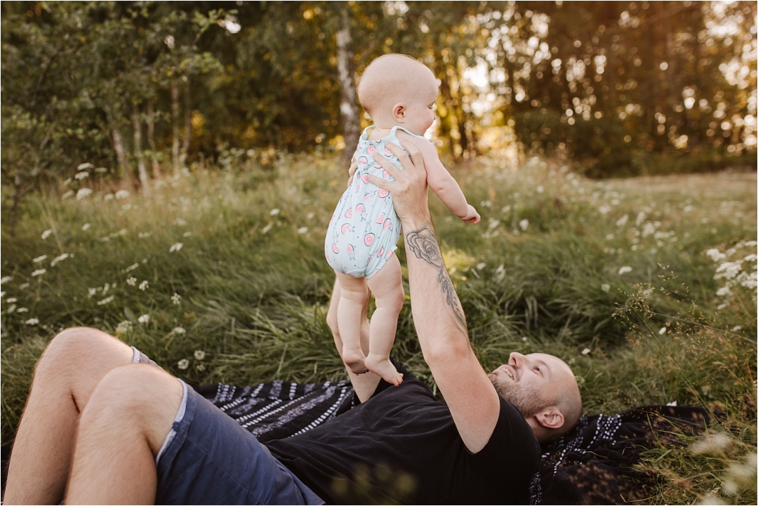 tata podnosi córeczkę narękach dogóry